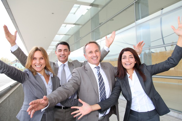 Group of happy business people with arms up
